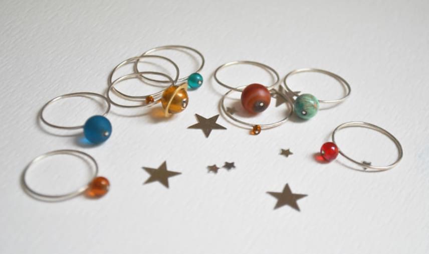A kézzel készített gyűrűk bolygói különféle kövekből, illetve üvegből készültek.