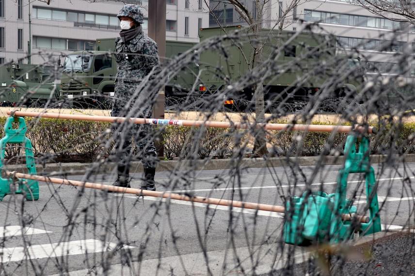 Japán katona őrségben harci járművek közelében a tokiói védelmi minisztériumnál 2017. március 6-án. A két Korea egyesítésének ügyeivel foglalkozó szöuli minisztérium vezetője kijelentette, hogy az észak-koreai rakéták megsértették az ENSZ BT határozatait.