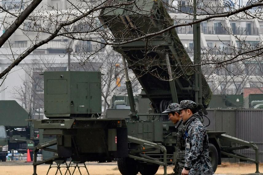A Japán Önvédelmi Erők egyik, PAC-3 típusú elfogó rakétával felszerelt harci járműve előtt mennek el japán katonák a tokiói védelmi minisztérium közelében. A japán kormányszóvivő elmondta, hogy a rakétaindítások súlyosan fenyegették Japán nemzetbiztonságát.