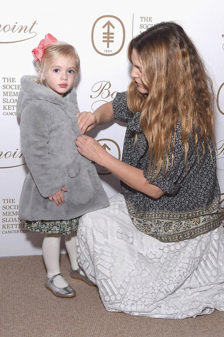 Igazi anya-lány pillanat: Drew Barrymore odaadóan gombolja be kislánya kabátkáját, nehogy megfázzon a szeszélyes márciusi időben.