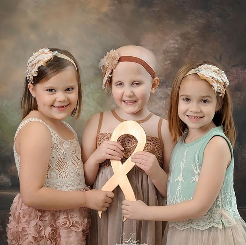 A lányok által közösen feltartott aranyszalag a gyermekrák elleni küzdelem jelképe. Ahogy fogalmaznak, a rák egy sárkány, a kemo a herceg, előbbi viszont a rossz hercegnőkkel kezdett ki.