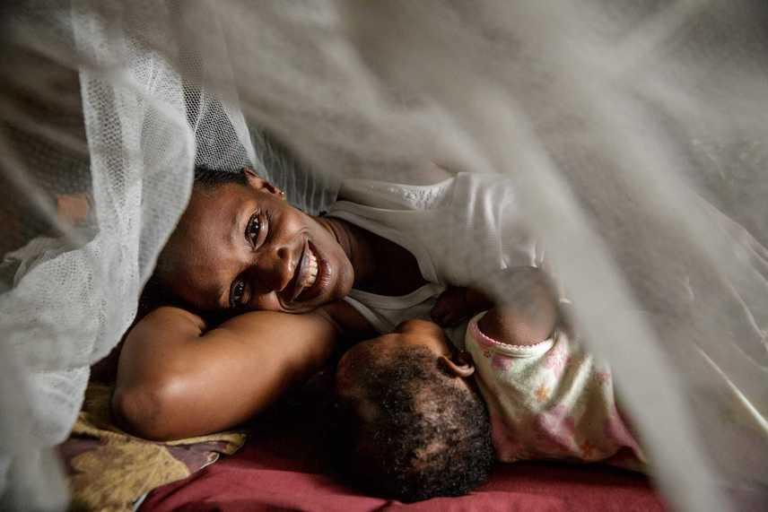 Sierra LeoneIssata és kisbabája háló alatt próbálják megvédeni magukat a moszkitócsípéstől.