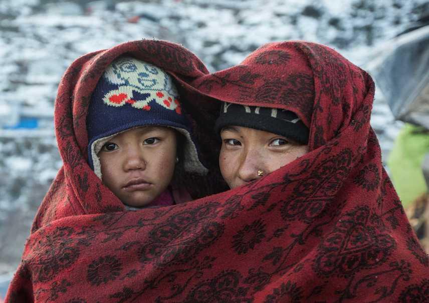 NepálMaya és lánya, Ritu a hideg időjárás elől bújtak a meleg takaró alá.