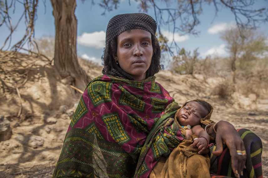 EtiópiaAisha harmadik gyermekével a karján, akit otthon, bába segítségével hozott világra.