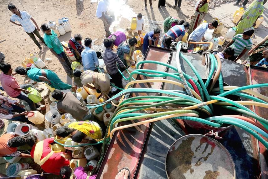 Helyi lakosok ivóvizet töltenek tartályaikba egy lajtos kocsiból a közép-indiai Bhopálban március 21-én, a víz világnapja előtti napon.