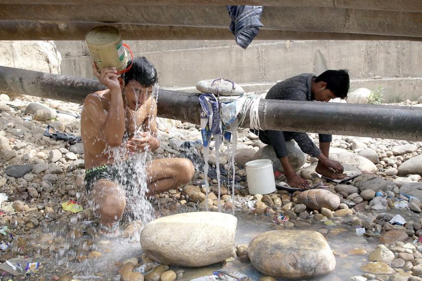 Két férfi tisztálkodik egy szivárgó ivóvizes vezetéknél. A kép ma reggel készült Dzsammuban.