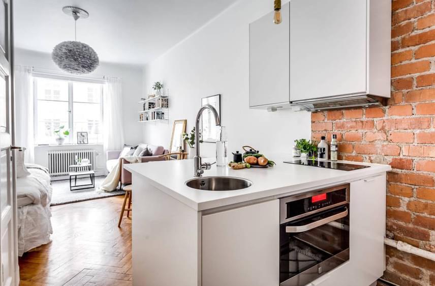 Apró, de praktikus a konyha, a téglafal pedig remekül oldja a fehér falak monotonitását. Csakúgy, mint a szürke és a rózsaszín árnyalatai.