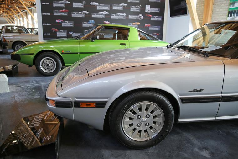 A háttérben az első generációs RX–7 sportkupé legelső verziója látszik, ami aranyosabb, mint az előtérben látható faceliftes kivitel, de az újabbnak van egy érdekessége: még a nyolcvanas években a Mazda repiajándéka volt egy bizonyos Felix Wankelnek
