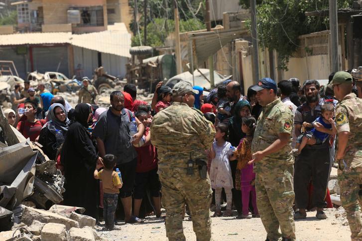 Iraki katonák vigyáznak az evakuált civilekre Moszul egyik ostrom alatt álló városrésze határán.