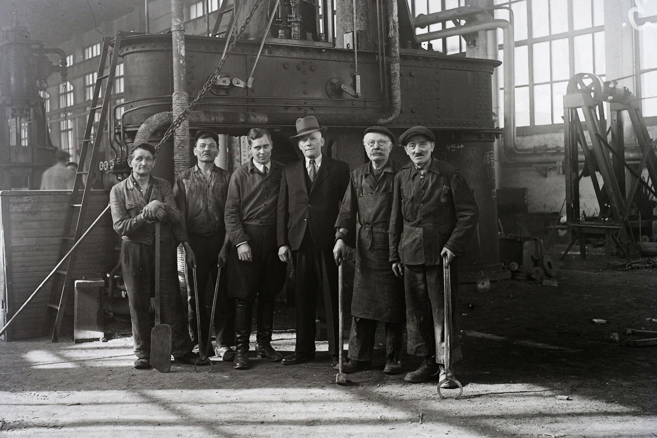 A gyárvezetés benéz a dolgozók közé: lovaglónadrágban és öltönyben a nehéz szerszámokat pihentető öreg szakik közt.