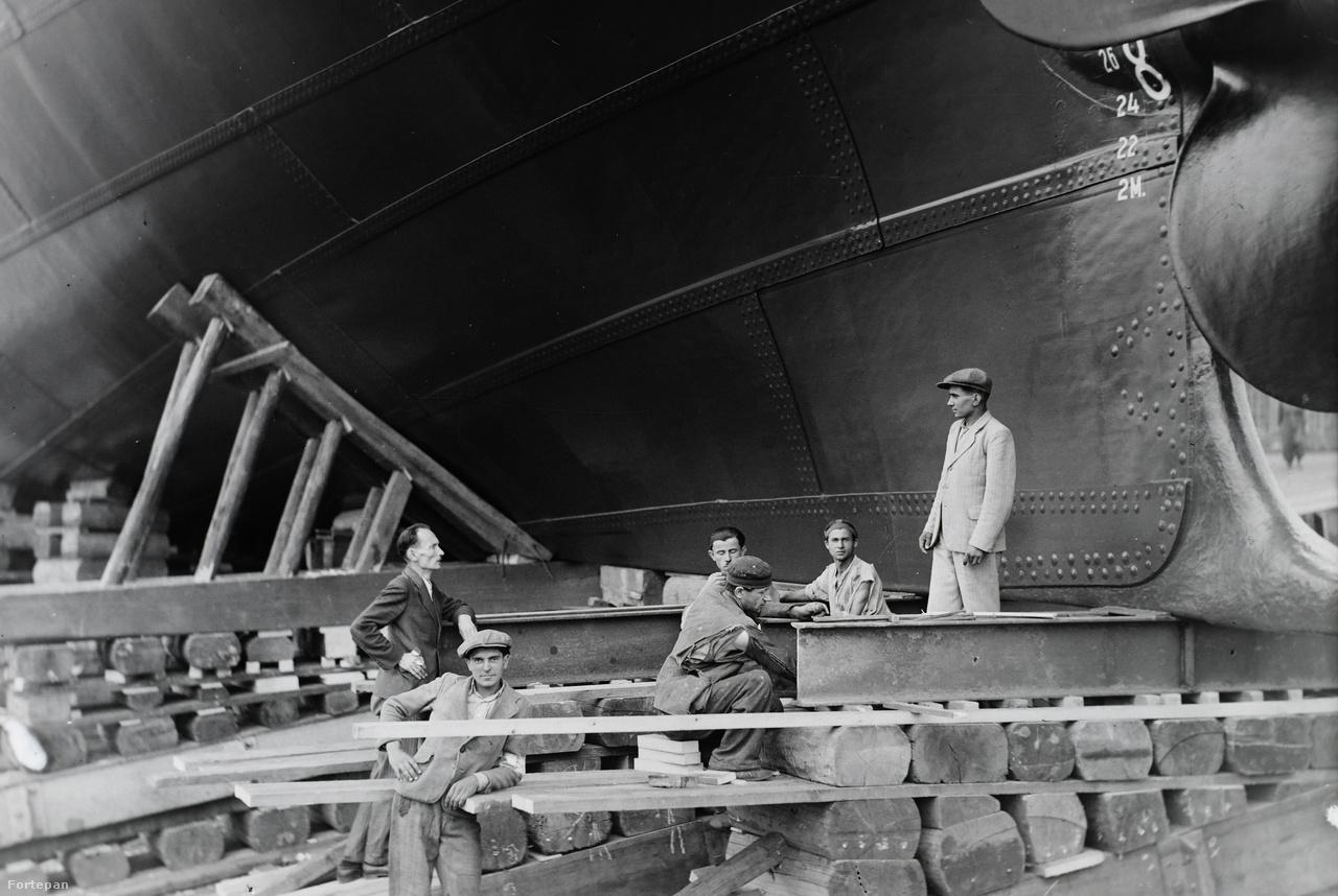 Szuggesztív csoportép a vízvonal alatt, a hajócsavar árnyékában. Az akkurátus szegecselés mintázata, a hajótestet alkotó lemezek textúrája igazán szépen kiemeli a munkások alakjait, arcélüket.