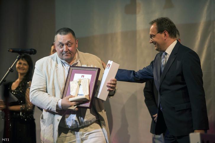 Vidnyánszky Attila a Nemzeti Színház Isten ostora című a legjobbnak értékelt darab rendezéséért átveszi az elismerést Hoppál Pétertől az Emberi Erőforrások Minisztériuma (Emmi) kultúráért felelős államtitkárától a 15. Pécsi Országos Színházi Találkozó (POSZT) díjátadó-ünnepségén Pécsen, 2015-ben