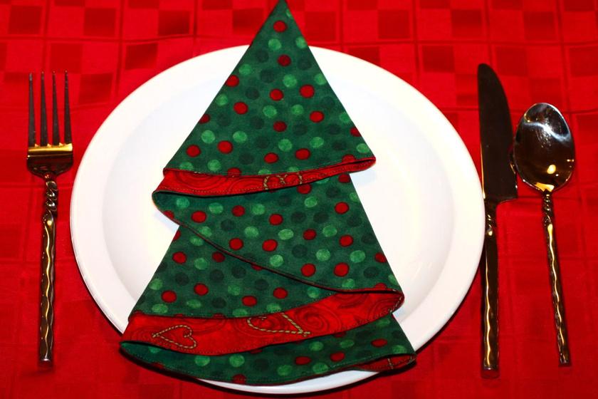 Hajts félbe egy kör alakú textilszalvétát, majd fogd meg az egyenes oldal felső harmadát és a kör alakú oldal alsó harmadát, és hajtsd össze újra. Ezt ismételd meg még kétszer, és kész is a szalvéta-karácsonyfa.