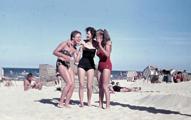 Az ötvenes évek divatjáról pedig azt írta a hölgy, hogy a nyári viselet fontos kelléke volt a vászon vagy karton fürdőruha.Karcsú és magasaknak kétrészes, teltebb és alacsonyabbaknak egybeszabott, aki többet akart takarni, annak pedig szoknyás variációkat is ajánlottak a divatszerkesztők.A fotón jól látható, hogy itt már a bikini és az egybe részes ruhát is viselnek a hölgyek
