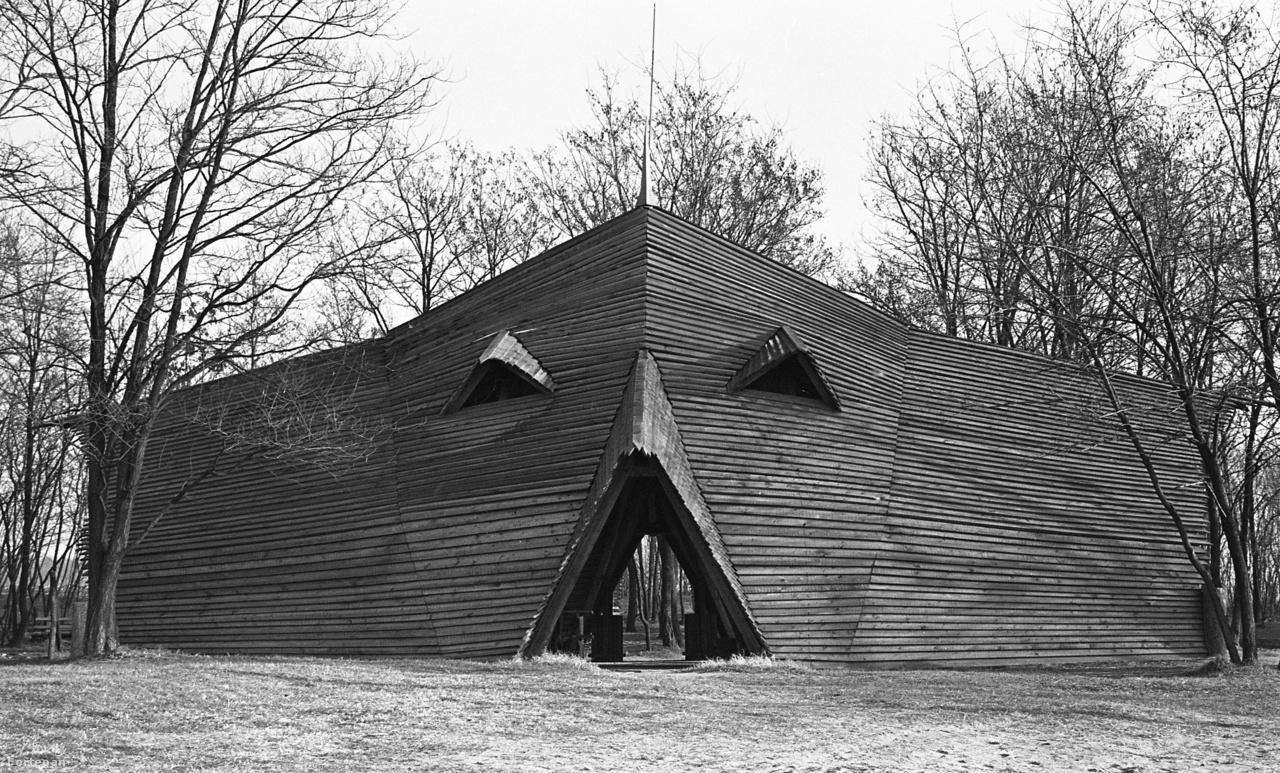 """Az azóta saját stílusát kialakító, nagyszerű építész, Ekler Dezső akkoriban még szorosan Makovecz Imre nyomában járt: házai sokban emlékeztettek mestere alkotásaira. Nem véletlen, hogy ez a szintén nagykállói táborhoz tartozó épülete bekerülhetett a Stern összeállításába is. (Igaz, Makovecz soha nem rakta volna ilyen katonásan-unalmasan a deszkákat.)Persze az, hogy az ingatlanhirdetésekben még ma is gyakran botlunk """"makoveczesnek"""" nevezett házakba (akkor is, ha azoknak nem sok köze van az építészhez), jól mutatja, mennyire jól megfogható, sajátos stílust alakított ki a 80-as évek végére."""