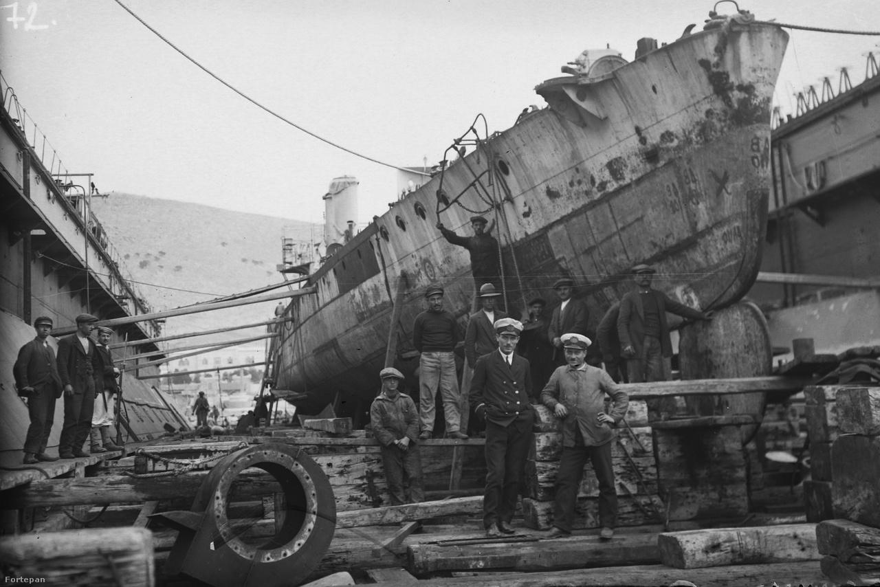 Csoportkép készülő hajóval. A kép a 20. század elején készülhetett, a bal szélen álló szuronyos puskás matróz, a munkások előtt álló hajóskapitány-szerű figura öltözéke is erre utal.