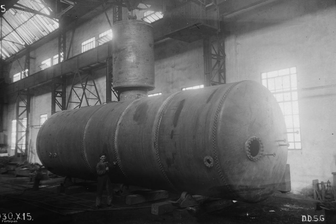 1930. október 15-én készült a kép az Óbudai hajógyárban. A hatalmas acéltartály mellett eltörpül a munkás, aki kalapáccsal és vésővel imitál munkát a szegecsek mentén.