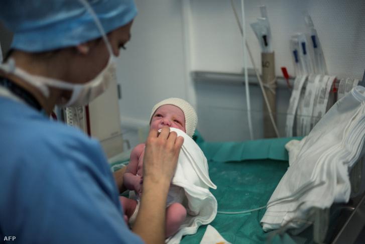 Újszülött babát törölget egy ápoló egy francia kórházban