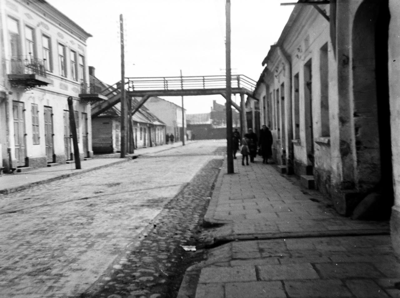 Egy ritka kép a gettóból, ahol amúgy tilos volt fotózni. A felvételen a skiernewicei Báthory István utcát (ulica Stefana Batorego) látjuk, az erdélyi fejedelemről és lengyel királyról elnevezett utca gyalogoshídja alatt gyerekek, asszonyok jönnek szembe. 1940-ben 6900 embert zsúfoltak össze a kijelölt területre. A kisvárosi gettó lakóit három évvel később a varsói gettóba szállították át. A döntő többség nem élte meg a háború végét.