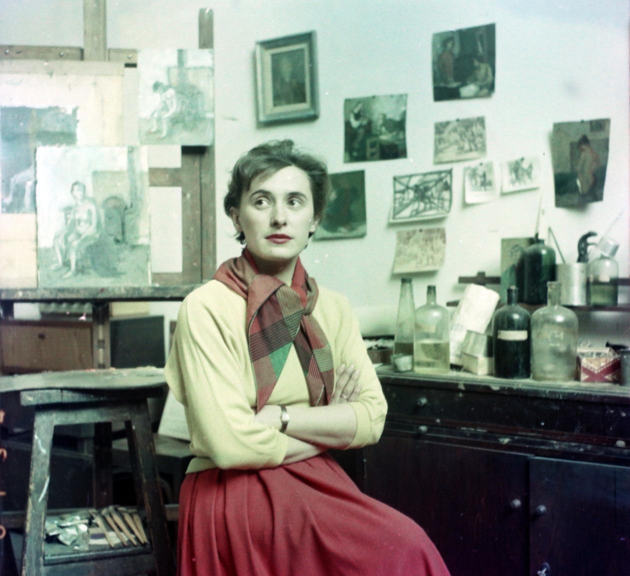 """Festőnő a Képzőművészeti Főiskola egyik Andrássy úti műtermében, 1956Túry Mária (1930–1992) 1948-ban kezdte a Képzőművészeti Főiskolát, ahol Konecsny György, Domanovszky Endre, Szőnyi István és Kádár György növendéke volt. Utóbbinak 1949 óta a felesége is, az ötvenes évek elején együtt tanítottak és közös műteremben alkottak. """"Anyám a negyvenes évek végén lelkes újjáépítő volt, a 'Fényes szelek' nemzedékével szárnyalt. Ehhez képest az ötvenes években politikai szerepvállalásából, harcosságából visszavett"""" – mesélte lánya, a szintén festőművész Kádár Katalin."""