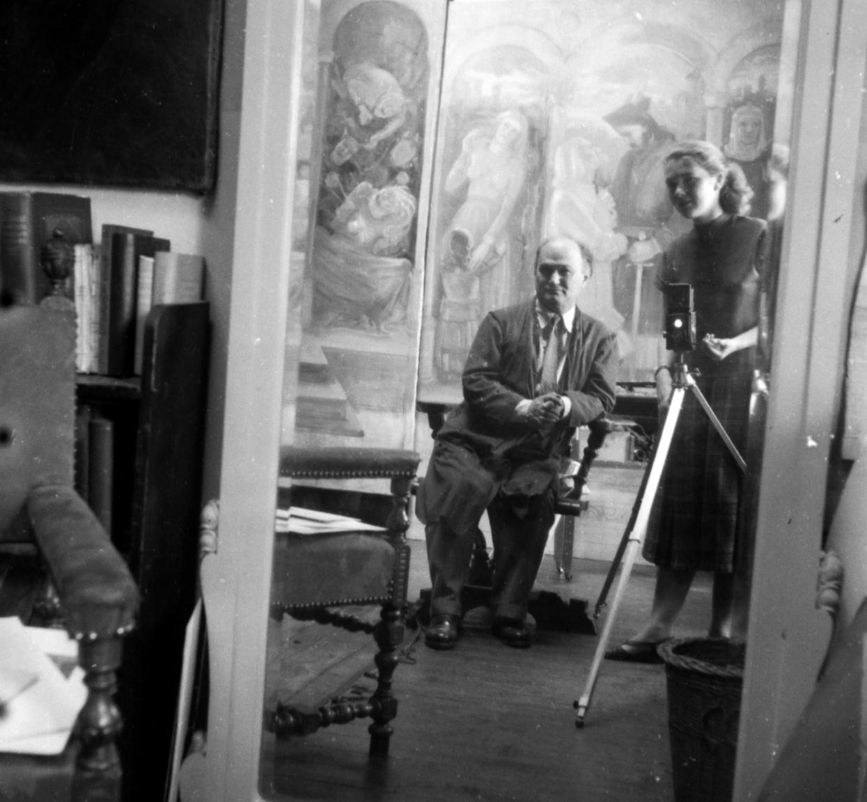 Akik már régóta ismerik egymást: Szenczi Mária és Ruzicskay György a festőművész-grafikus  epreskerti műtermében. Háttérben a Bánk Bán és Tiborc című műRuzicskay György (1896–1993) Szarvason született, sok külföldi tanulmányút, évtizedes viharok után végül 1960-ban ide tért vissza. Munkáinak egy részét még életében múzeumban helyezték el.                         A fotókon szereplő festmények hollétéről semmit sem tudni, viszont a Ruzicskay Alkotóház állandó kiállításában egy-egy kisebb méretű pasztell másolat található róluk. A Bánk bánhoz való kapcsolatáról annyit sikerült csak kideríteni, hogy a dráma 1946-os nagyváradi bemutatóján Ruzicskay tervezte a díszleteket.