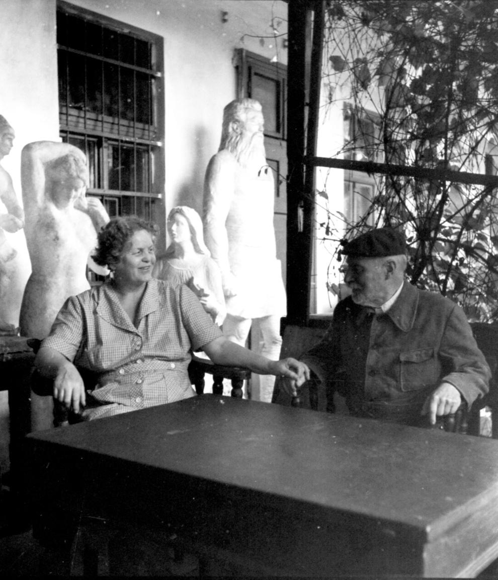 """Medgyessy Ferenc szobrászművész és felesége a Százados úti műterem verandáján 1956-banMedgyessy Ferenc (1881–1958) is a telep első lakói közé tartozott. A háttérben jobbra Hermann Ottó szobra magasodik, mely ma a róla elnevezett miskolci múzeum előtt áll. Feltehetően ez volt Medgyessy Ferenc utolsó műve.Balra a Debreceni Vénusz egyik változata áll. Az 1940-es évek óta a szobrász számtalan verzióban készítette el ezt a művét. A haját igazító aktszobor névadója Móricz Zsigmond, Medgyessy debreceni iskolatársa volt. A kortársak azt mondták, felesége """"megelevenedett Medgyessy-szobor volt"""". 1931-ben Csorba Géza ismertette össze az akkor ötvenéves szobrászt és a harmincéves özvegyet. Az orosz származású Maria Alekszandrova Djakonovának rögtön szimpatikus lett a férfi, aki """"szereti az orosz népet s mindent,"""