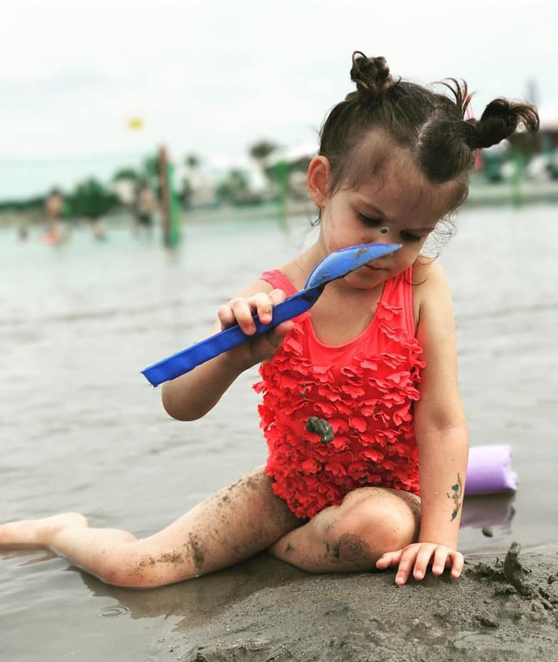 Ördög Nóra kislánya fodros kis fürdőruhájában nagy koncentrációval építkezik a strandon.