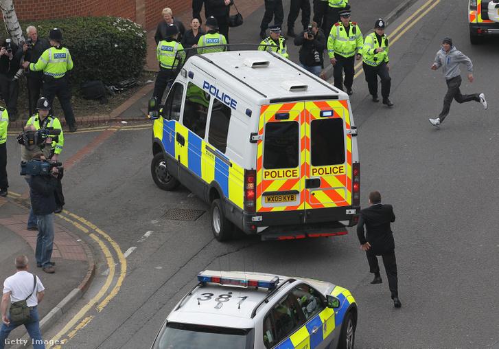 Halliwellt szállító a bíróságra szállító rendőrautó, tüntető helybéliekkel körülvéve, 2011. március 28-án.