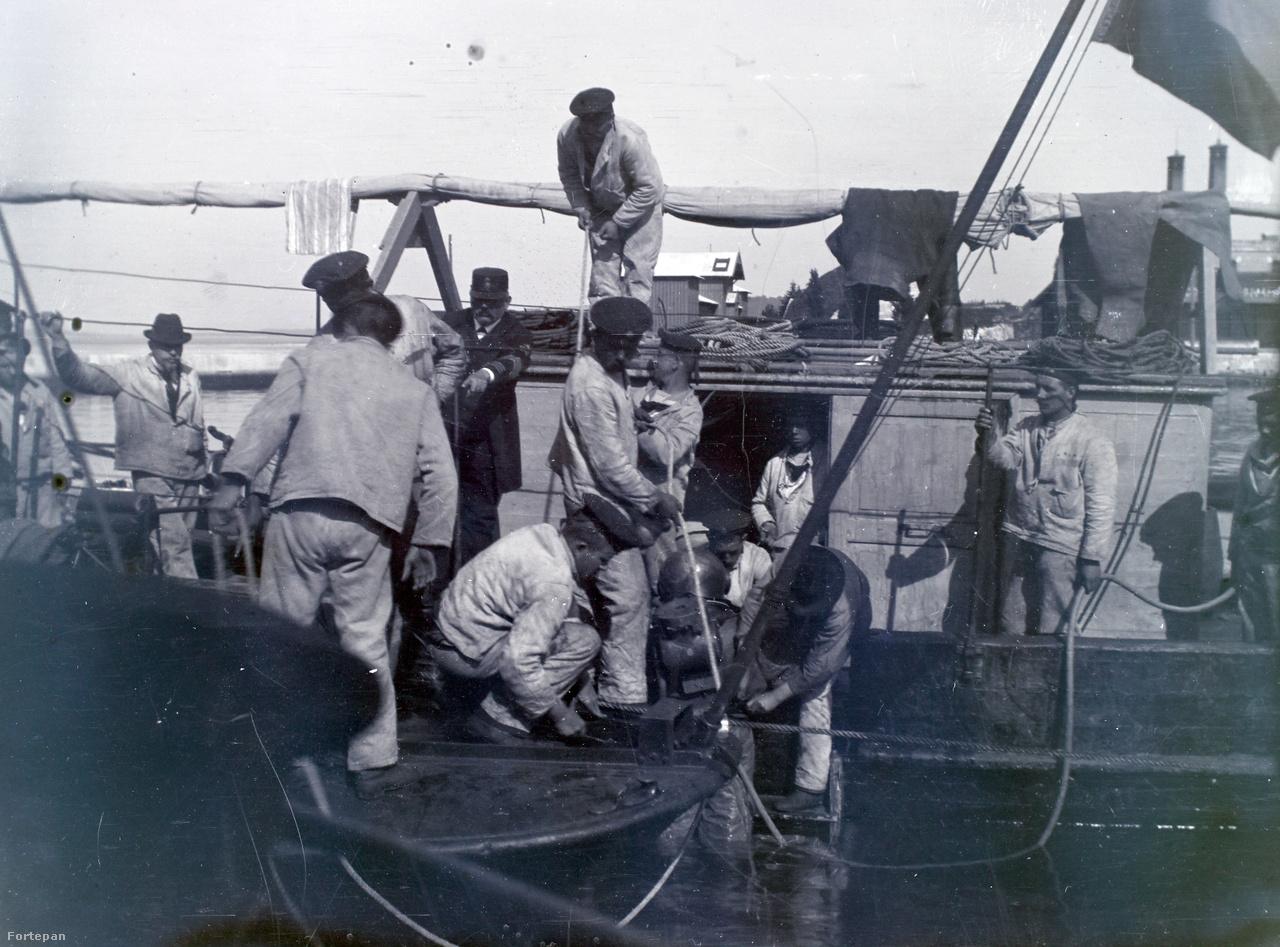 Nehéz búvárfelszerelést viselő ember ereszkedik épp a vízbe egy hajó fedélzetéről.