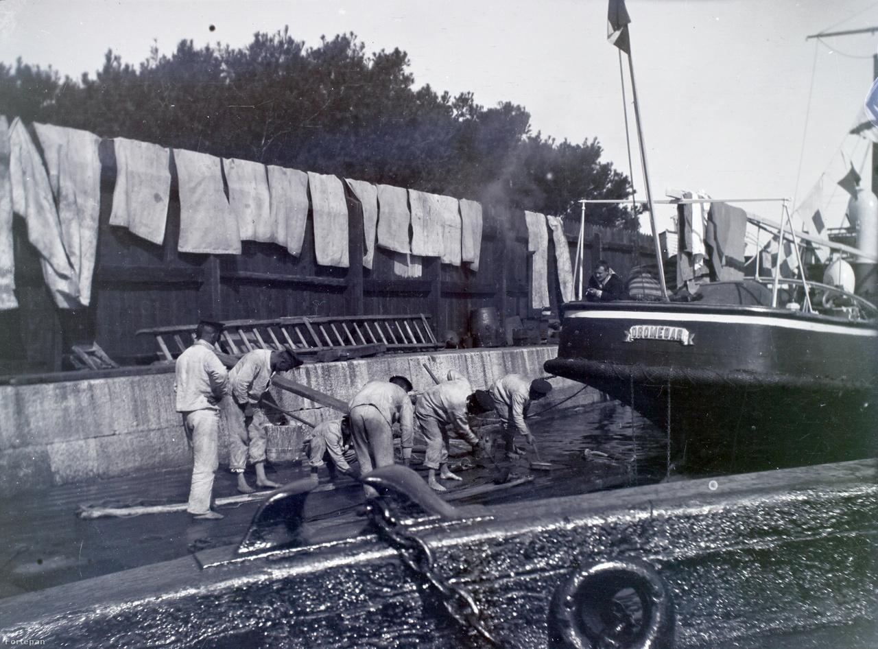 Takarító matrózok és kerítésen száradó vásznak kölcsönöznek némi otthonosságot a kikötői életképnek. A Dromedar tatjáról kihajoló, cigizgető tengerész valószínűleg hasznos tanácsokkal segíti a munkát.