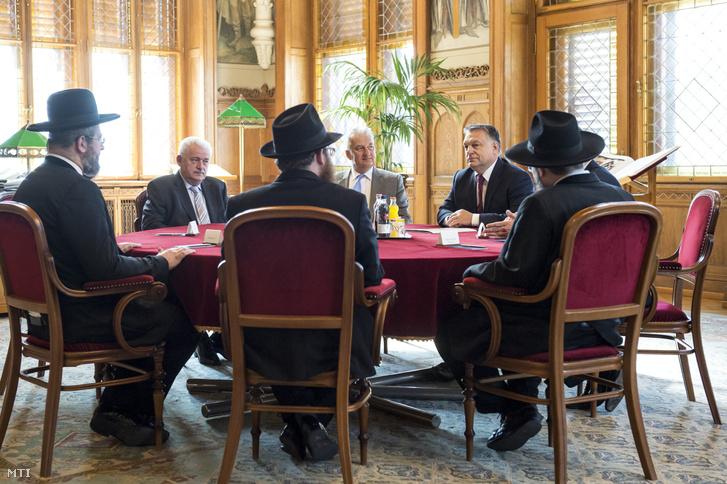 A Miniszterelnöki Sajtóiroda által közreadott képen David Lau Izrael askenázi főrabbija (b) és Orbán Viktor miniszterelnök (szemben j) találkozója az Országházban 2017. július 6-án. Az asztalnál Fónagy János, a Nemzeti Fejlesztési Minisztérium parlamenti államtitkára (szemben b) és Semjén Zsolt nemzetpolitikáért felelős miniszterelnök-helyettes (szemben k,) valamint Köves Slomó, az Egységes Magyarországi Izraelita Hitközség (EMIH) vezető főrabbija (b2 háttal) és Oberlander Baruch, a Budapesti Ortodox Rabbinátus és a Chabad Lubavics mozgalom vezetője (j háttal).