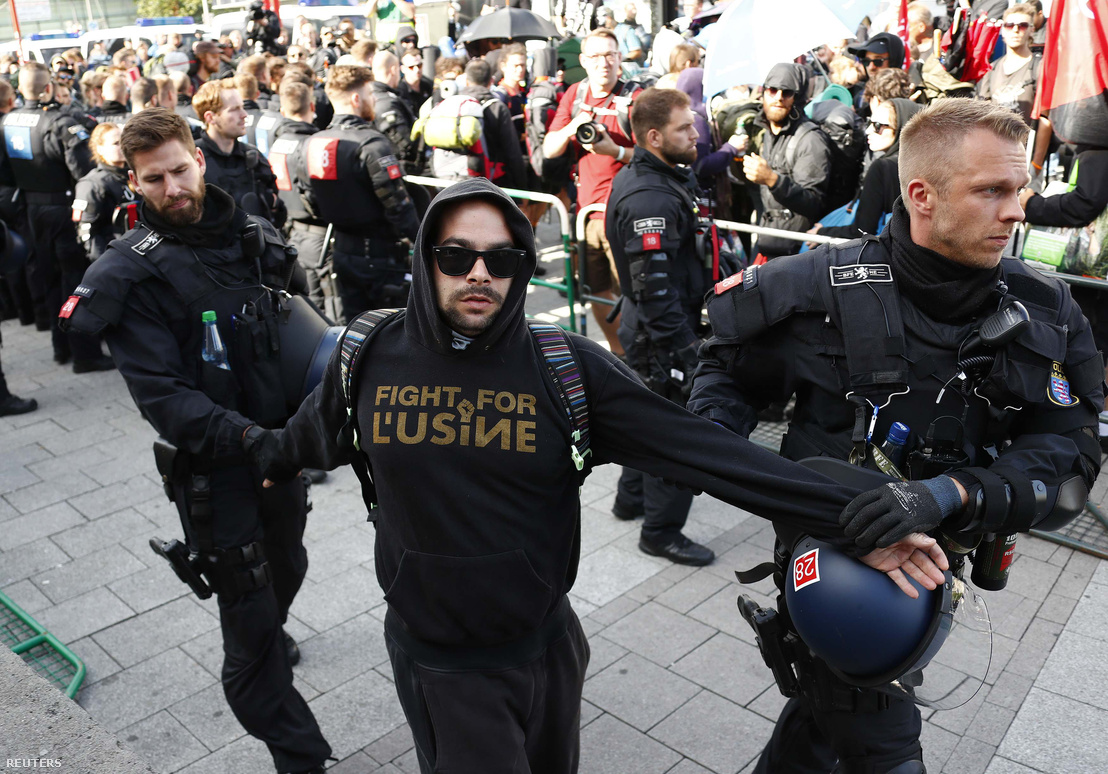 Egy tüntetőt állítanak elő rendőrök a hamburgi pályaudvar közelében, nem sokkal azután, hogy leszállt a vonatról