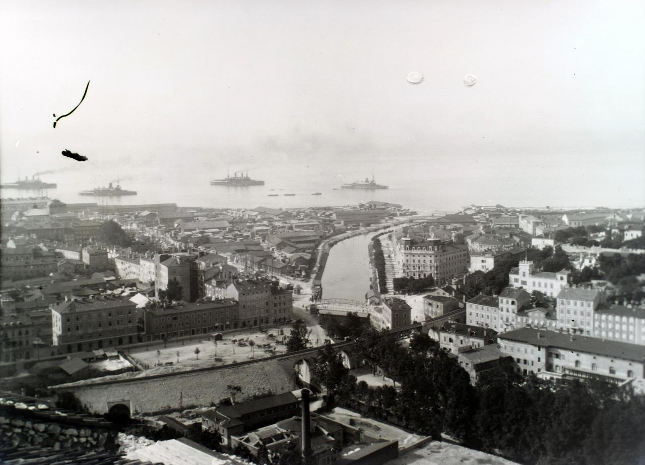 Fiume látképe egy közeli magaslatról. A horizontot a császári és királyi haditengerészet hajóinak füstje homályosítja el.