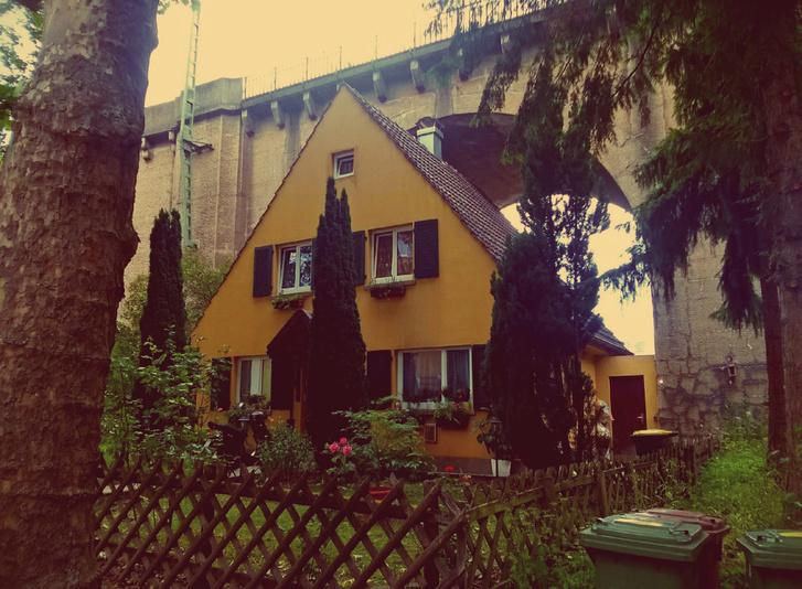 A kis sárga ház a vasúti híd alatt Németország déli részén van a kommentek szerint (https://redd.it/6l1yy9)