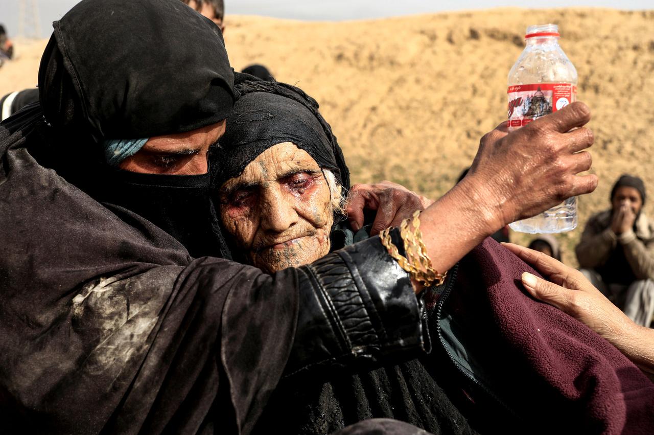 Moszul nyugati külvárosában  készült ez a kép. A 90 éves Khatla Ali Abdallah családjával menekült el a városból, az unokái cipelték át a nőt a sivatagos területen. Úgy néztek ki, mint akik napok óta nem ettek és ittak semmit. A nő nem tudott állni, de még ülni is alig. Mivel csak a fényképezőgépem volt nálam, nem tudtam segíteni rajtuk. Megkönnyeztem ezt a találkozást.                         Pár nappal később megtaláltam őket egy menekülttáborban, ahol már tudtunk beszélgetni. A nő elmondta nekem, hány konfliktust élt már túl a városban az elmúlt évtizedekben, és, hogy ez a mostani egyikhez sem volt fogható. Menekülésük előtt napokig várakozott a házuk pincéjében, amíg felettük az utcán átvonult a háború. Legjobban azt sajnálja csak, hogy mind a 20 tyúkját hátra kellett hagynia.