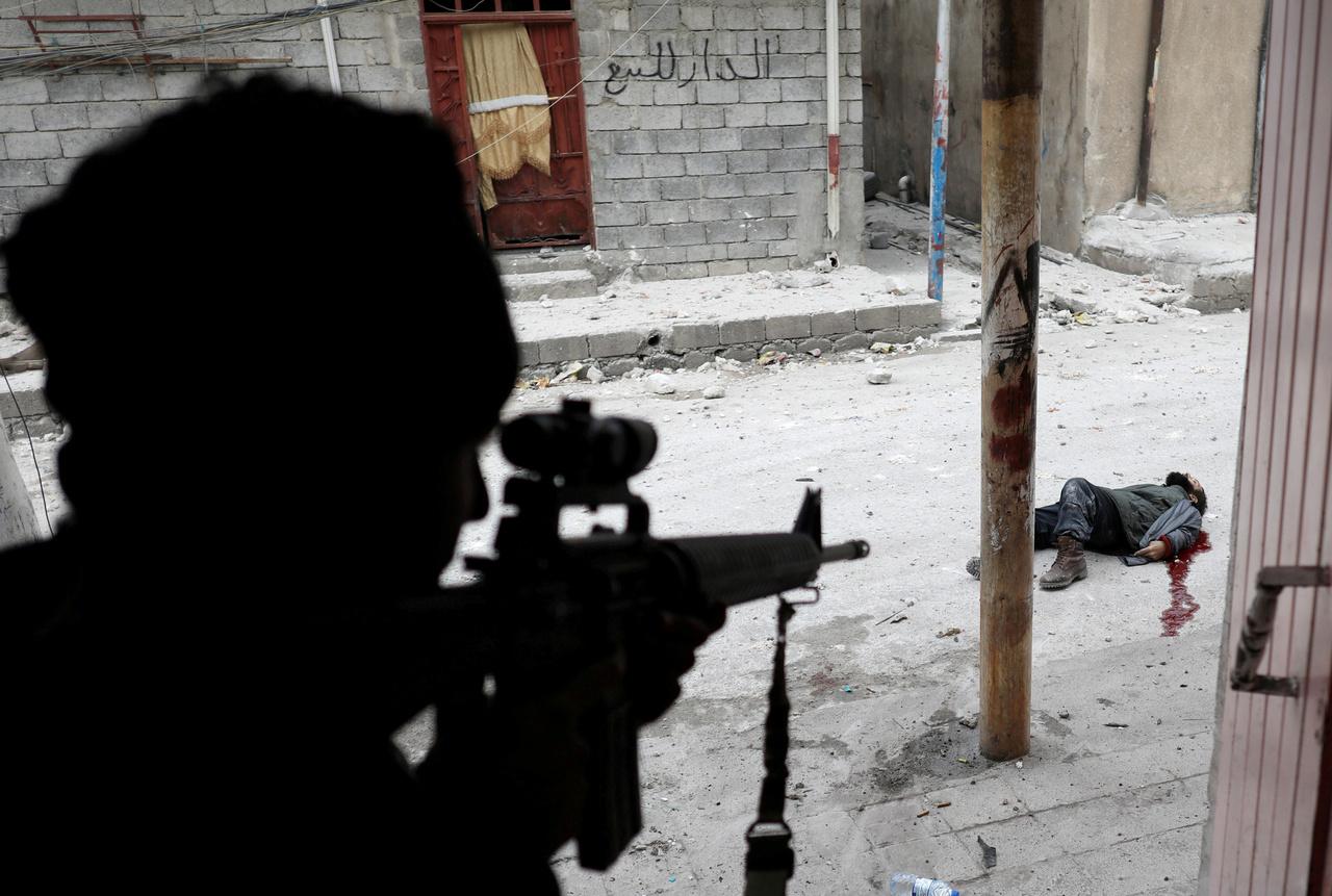 Az iraki csapatokat kísértem a nyugati városrészben. A sokadik közös utunk volt, megszoktak már a katonák és egészen közel engedtek az akcióhoz. Házról házra haladtunk szűk mellékutcákban, amikor az egyik sarkon tüzet nyitottak ránk az Iszlám Állam katonái. Berohantunk a legközelebbi házba, de futás közben hátba lőtték az egyik társunkat, egy másikat pedig mesterlövész lőtt fejen, miközben beszélgettünk. Órák teltek el, mi pedig mozdulatlanul gubbasztottunk a házban. Már lement a nap, mire erősítést és légi támogatást kaptunk. Ekkor kezdett a ház felé szaladni egy öngyilkos merénylő.  A mellettem álló katona lőtte le az ajtóból, én pedig ezt a képet készítettem pillanatokkal a lövés után.                          Sok év rutin van a hátam mögött, de ez extrém durva közelharc volt. A házból csak másnap merészkedtünk ki naplemente után, hogy visszavonuljunk a bázis felé.