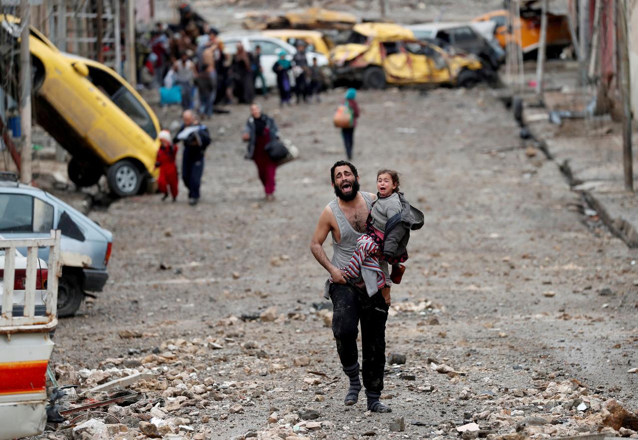 A lányát cipeli egy férfi Wadi Hajar egyik lebombázott utcáján. A szomszédaikkal együtt menekültek a házaikból, amikor a környékre benyomultak az iraki különleges erők és tűzharcba keveredtek az Iszlám Állam gerilláival. A lányon műanyag szandál volt, az apja zokniban menekült, de sokan csak mezítláb követték őket. Amikor a civilek elérték az iraki védvonalat, a férfiaknak le kellett vetkőzniük, hogy biztos legyen, hogy nem öngyilkos merénylők. A bepánikolt apa és a lánya mindketten egy közeli menekülttáborba kerültek.