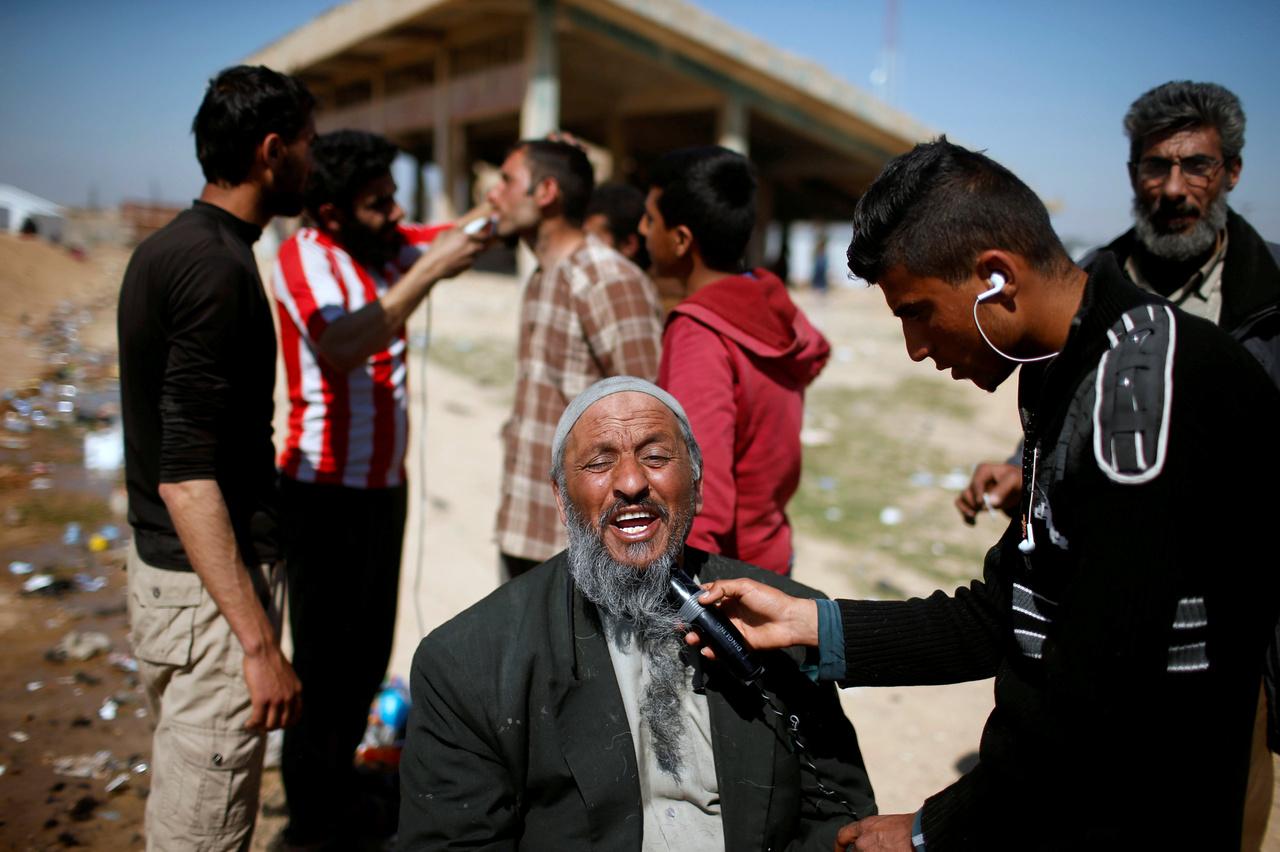 Egy menekülttáborban sétálgattam Moszul déli részén, amikor feltűnt, hogy minden férfi a szakállát borotválja. Az Iszlám Állam uralma alatt kötelező viselet volt a hosszú szakáll, a táborban így mindenki boldogan ugrott a borotvák alá, de a képen látható társaság először nem engedte, hogy fotózzam is őket, mert féltek az Iszlám Állam megtorlásától, ha a gerillák visszafoglalnák a környéket.