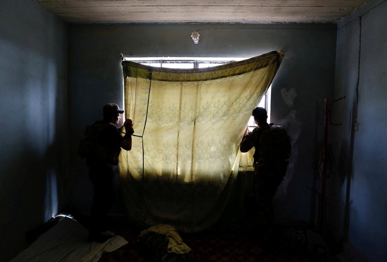 Egy nappal korábban vert bázist az épületben az iraki csapatok egyik különleges egysége. A földön takarók és gyerekjátékok hevertek szanaszét, amik az üres töltényhüvelyekkel mellett különösen szomorú összképet mutattak. Lepedőből készült a sötétítő az ablakra, amit félrehúzva a két katona a közeli házakat fürkészte, ahová az egyik társuk ment át felderíteni. A környék tele volt mesterlövészekkel, ezért nem volt tanácsos beállni az ablakok elé. Ez egy eseménytelen és csendes pillanat volt, ami azért beszédes mégis, mert semmi nem történt, de bármilyen tragédia megtörténhetett volna.