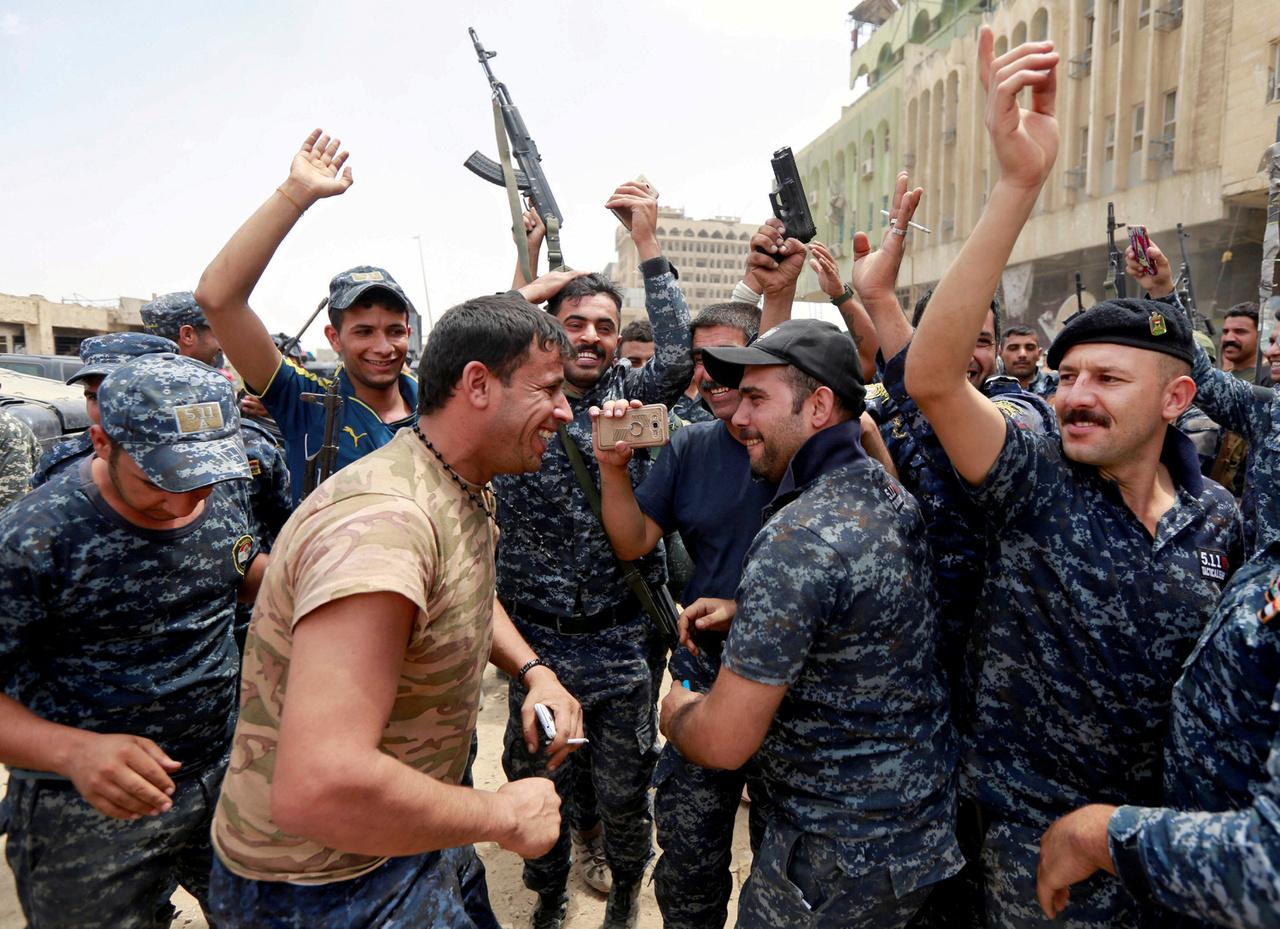 Boldog iraki katonák a 9 hónapos offenzíva utolsó napjaiban. Ez volt az első alkalom, hogy nyilvánosan ujjongtak az egyenruhás katonák, amikor a város felszabadítását hivatalosan is bejelentették. Mindenki a levegőbe lövöldözött, és ünnepelt. A golyóálló mellény viszont mindenk újságírón rajta maradt még a tűző nap és a kánikula ellenére is.
