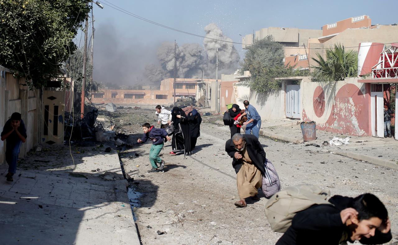 Moszul Tahrir negyedében sétáltunk, ahol korábban többször is megfordultam már. Ez a terület közel van a frontvonalhoz, nehéz volt megközelíteni a törmelékek és a folyamatos harcok miatt. Csendes volt a környék, amikor megérkeztünk, leszámítva egy autóba rejtett pokolgépet, ami nem sokkal korábban robbant fel a benyomuló csapatok mellett. Az emberek csak a harcok közötti rövid szünetekben merészkedtek az utcára, többnyire ilyenkor próbálták elhagyni az otthonaikat. A képen látható tömeg is megindult az iraki csapatok felé, amikor hirtelen lecsapott a légierő a szomszédos utcákra. A gépeket csak pillanatokkal a robbanás előtt lehetett észlelni, úgyhogy a detonáció hirtelen hatalmas pánikot okozott az utcán. Mindenki szaladni kezdett, én is fedezékbe vonultam, mielőtt fotózni kedztem, mert nem lehetett tudni, jön-e újabb támadás.