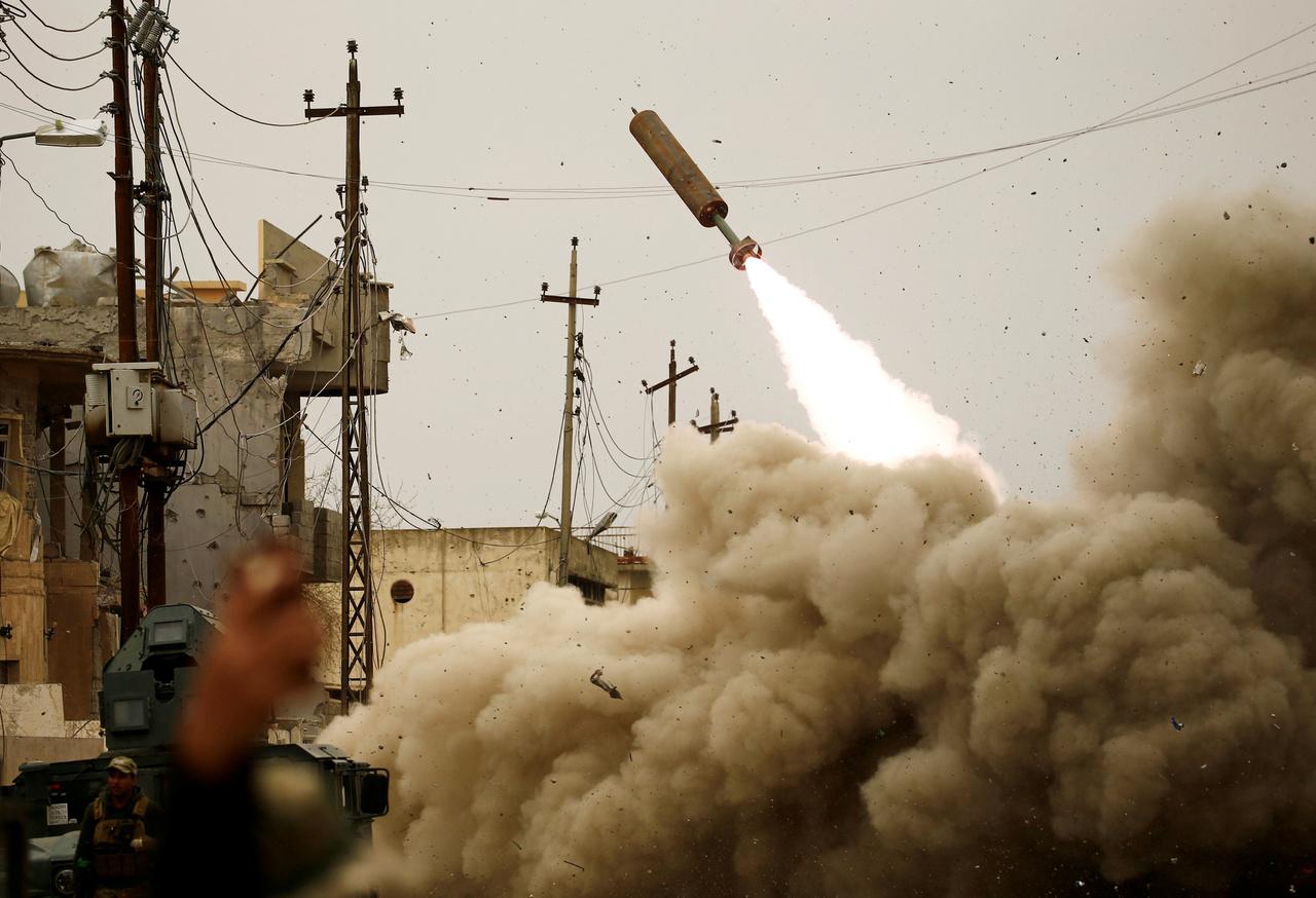Egy moszuli kormányépület területén harcoltak az iraki csapatok, amikor az Iszlám Állam egyik drónja repült el felettünk. Mindenki azonnal fedezékbe vonult bombatámadástól tartva. Megvágtam a kezem, úgyhogy visszaindultunk a kocsihoz, hogy elhagyjuk a területet, ott kaptam el ezt a jelenetet, ami az iraki csapatok válaszlépése volt. Ezt a rakétát lőtték vissza az Iszlám Állam egyik feltételezett búvóhelye felé.