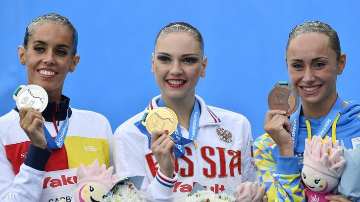 A győztes orosz Szvetlana Kolesznyicsenko (k) a második helyezett spanyol Ona Carbonell (b) és a harmadik helyezett ukrán Anna Volosina a szinkronúszás egyéni technikai döntőjének eredményhirdetésén