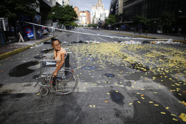 Kerekesszékes nő egy metrójegyek borította úttesten a Nicolás Maduro venezuelai elnök alkotmánymódosítási törekvéseit ellenző 24 órás általános sztrájk idején Caracasban 2017. július 20-án. 2002 óta először tartanak általános munkabeszüntetést a súlyos infláció és élelmiszerhiány sújtotta dél-amerikai országban.
