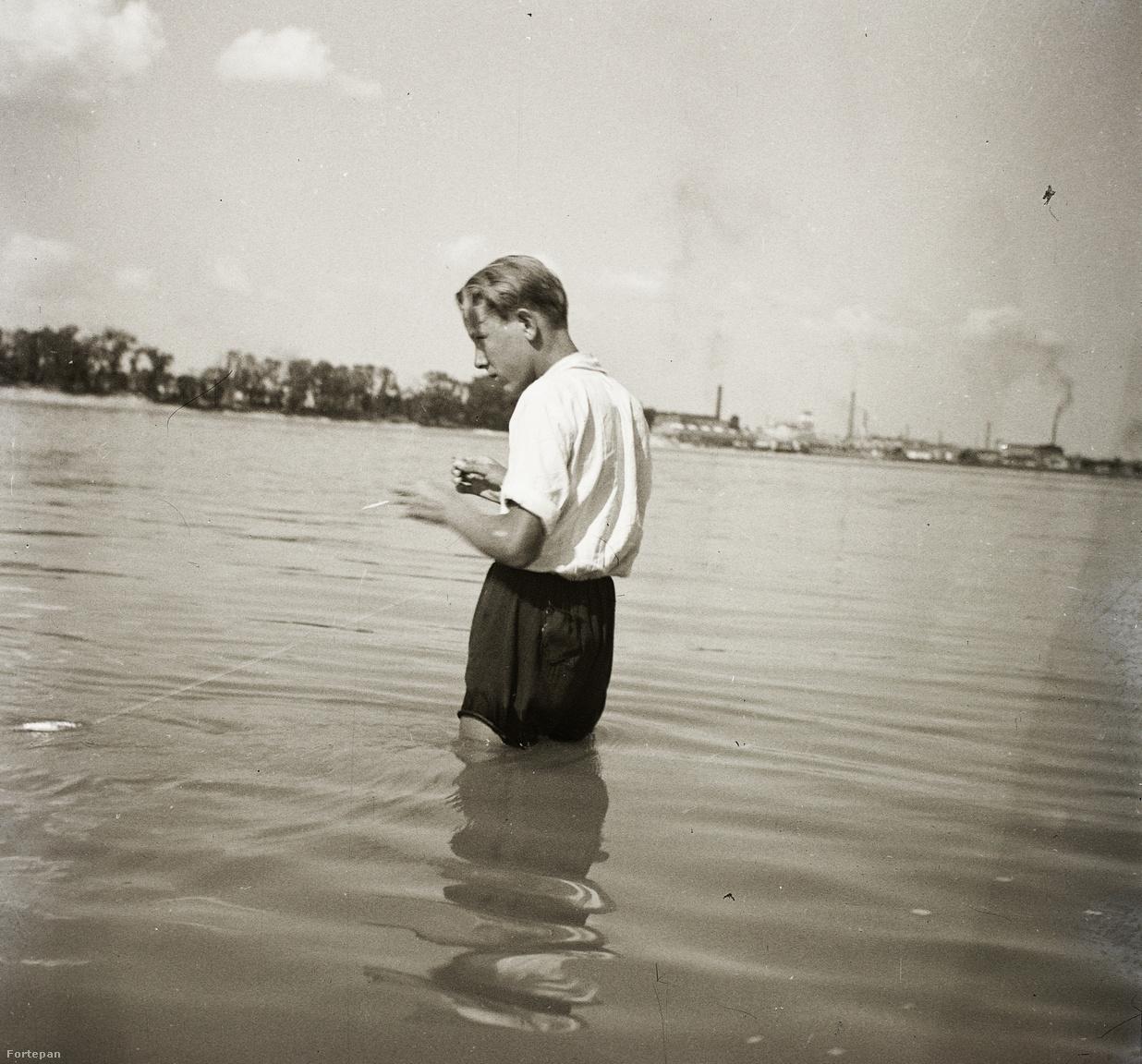 """A cigarettázó kocahorgászt ábrázoló kép 1935-ben készült, vélhetően a Római-part környékén, szemközt mintha az újpesti cérnagyár kéménye füstölögne. Horgászunk bot nélküli szerelékkel, népies nevén """"zsebpecával"""" próbálkozik. Bizonyára még nem tapasztalta meg, hogy a cigaretta nem túl szerencsés aktív horgászat közben, mert könnyen elégeti a vékony műanyagzsinórt. Bár az évszámból ítélve lehet, hogy inkább vastagabb cérnát használ, amit talán a szemközti gyárban készítettek."""