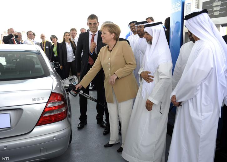 Angela Merkel német kancellár (k) metángázzal feltankol egy autót amikor egy avatóünnepségen elindítja az első földgáz kutat az Abu-Dzabitól 30 km-re fekvő Mazdarvárosban 2010. május 25-én. A gáztöltőállomás az első szén-dioxid-mentes egyesült arab emírségekbeli város tiszta levegőjét szolgálja.