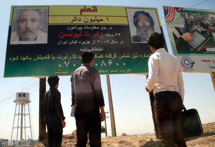 Afgán férfiak néznek 2012. április 24-én a nyugat-afganisztáni Herátban egy óriási hirdetőtáblát amely jutalmat ígér bármilyen információért Robert Levinson nyugalmazott FBI-ügynökről akinek nyoma veszett 2007. március 8-án az iráni Kish szigeten