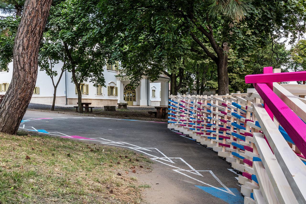 """9. KEREKÍTÉS (Széchenyi István Egyetem) A győri egyetemisták a tállyai Mailloth-kastély parkja és az iskolaudvar elválasztására szolgáló rozzant és rossz emlékű drótkerítés helyett terveztek mobil, játszóeszközként is használható kerítést. A flexibilis szerkezet egyben """"területfoglalás is"""", amely játékos vonalvezetésével csippent némi teret az amúgy is beszorított udvaron játszó iskolásoknak."""
