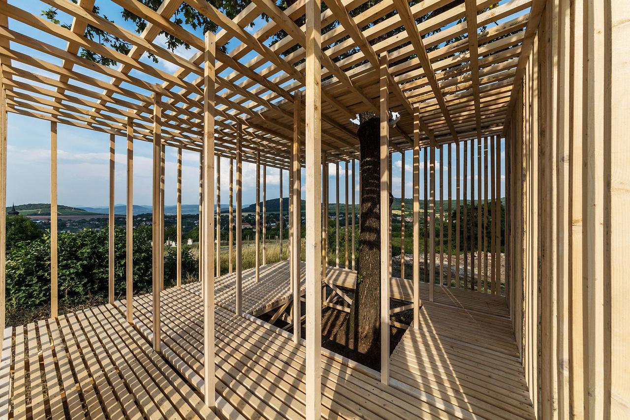 """6. MERENGŐ ÉS PLETYKAPADOK(Moholy-Nagy Művészeti Egyetem) A MOME hallgatói többszörösen meghatározott szakrális teret alakítanak ki installációjukkal. A Kálvária-dombon egyedül álló fa tövéből nagyszerű kilátás nyílik a falura. A látvány lenyűgöző, miközben még a háttérben a falu múltja, a halottak emléke kísért. A népmesékből, legendákból ismert égig érő fa mítosza és a varázslók fája ihlette a meditációra, elmélyedésre vagy csak egyszerűen pihenésre késztető szerkezetet, amely körülöleli, védi a """"szent"""" fát, valamint pihenőhelyeket is képez."""