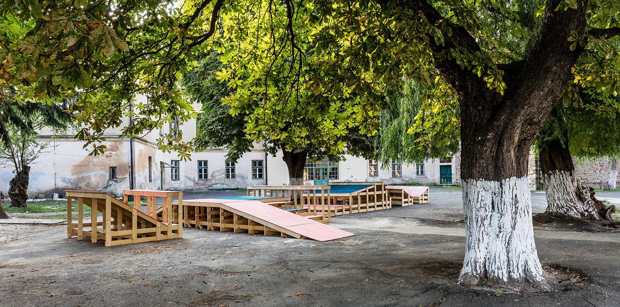 1. MONOKIPADDAL (Budapesti Metropolitan Egyetem)Az egyetem hallgatói két helyszínre terveztek installációt, az egyiket Monokra, ahol az iskolaudvart alakították át, ahová a tanulók szünetekben és tanítási idő után kiszabadulnak. A gyermekek mozgásigényét kihasználva és átgondolva terveztek bicikli- és gördeszka pályát a METU hallgatói, olyan mobil szerkezetet, amely leülésre, lerakodásra is alkalmas, és kényelmesen, védetten (pl. esőtől) elfér az iskolai felszerelés benne.A játékos sport mellett az építmény ideiglenes színpaddá is alakítható az iskolai rendezvények számára. Plusz csavar az installáció kialakításában, hogy összerakott állapotában MONOK falu nevét adja ki a vázszerkezet, reflektálva ezzel a Hello Wood egy korábbi 2012-es workshopjára, amelynek a tipográfia is témája volt.